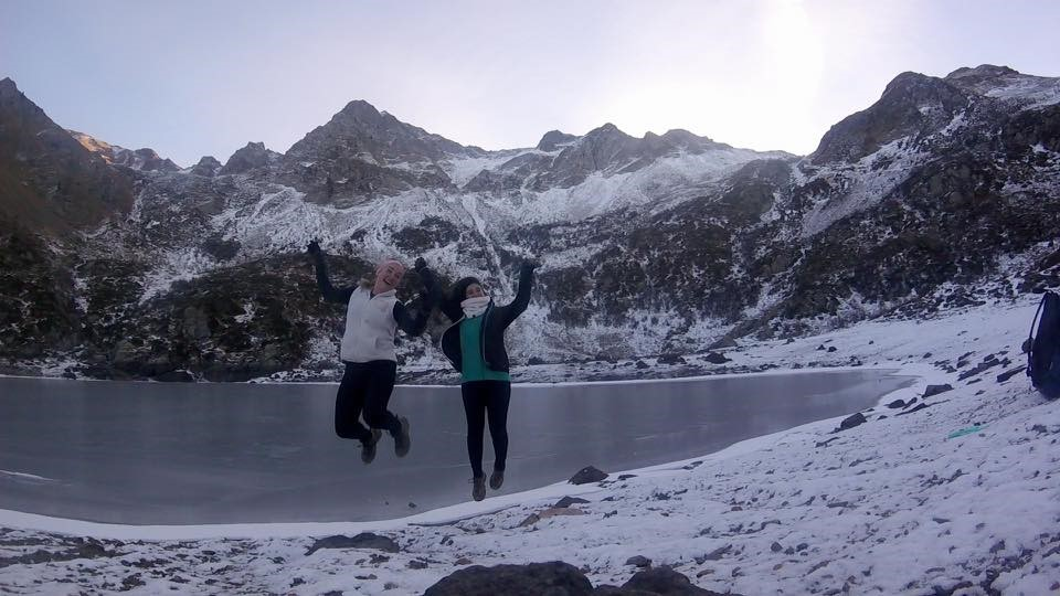 Miranda and Camila jump alongside a snowy, mountainous lake.