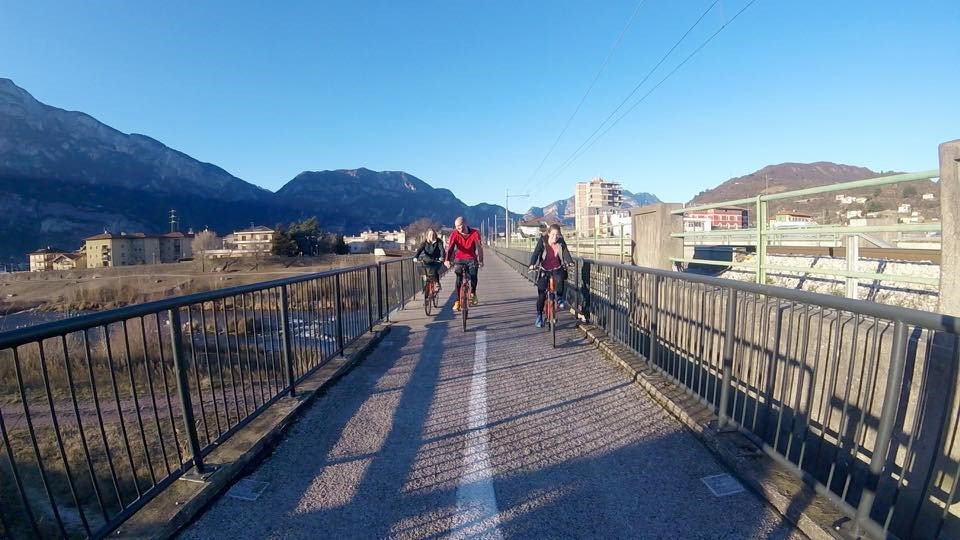Three students on bike trail in front of buildings and mountains.
