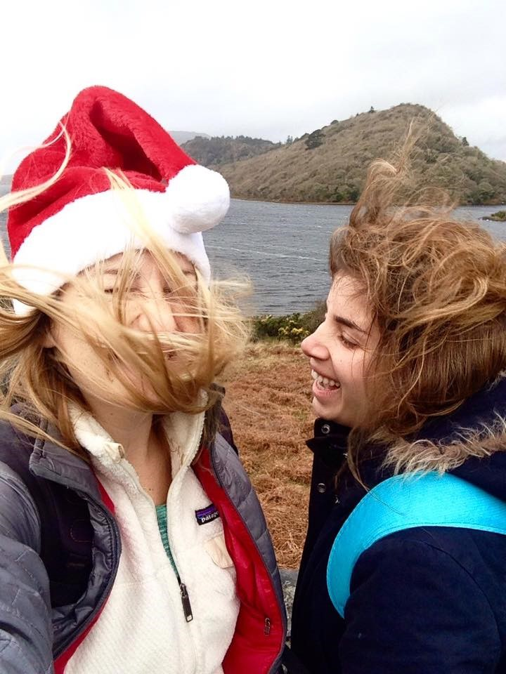 Miranda and Gili laughing with hair blowing in front of water and mountains.