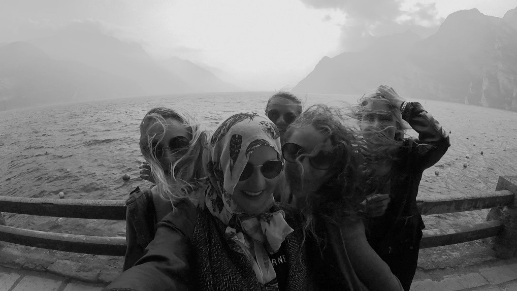 Friends in front of a windy, foggy lake.