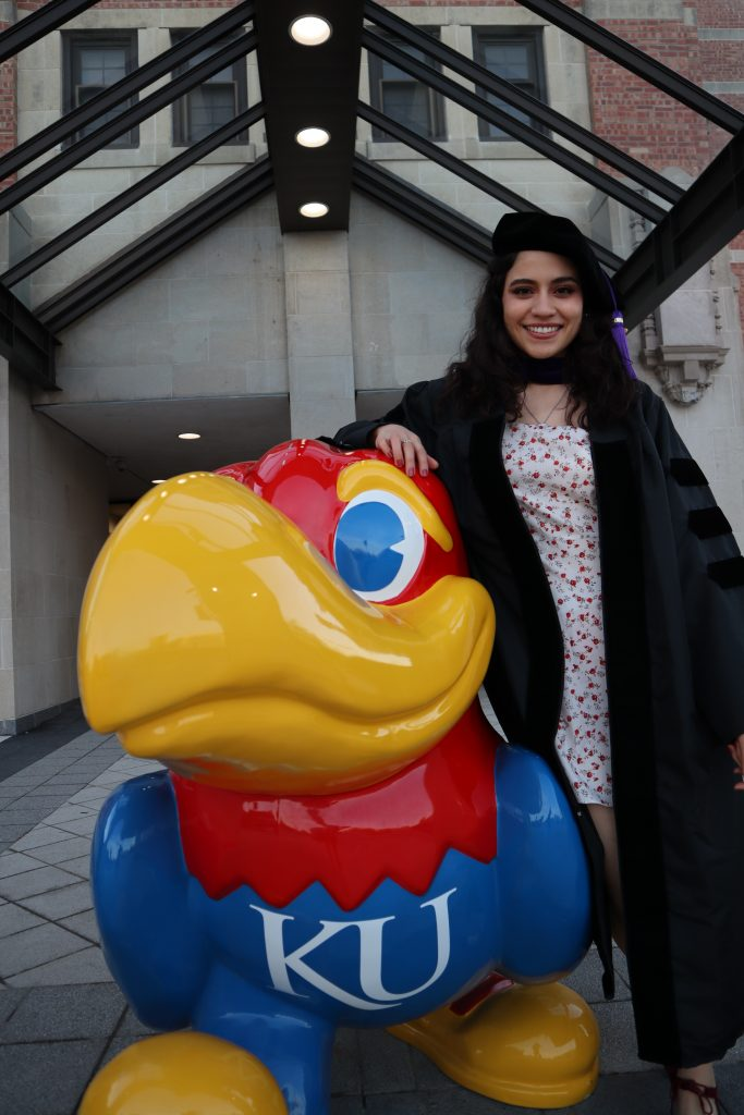 Samantha Natera in law graduate regalia next to a Kansas Jayhawk statue