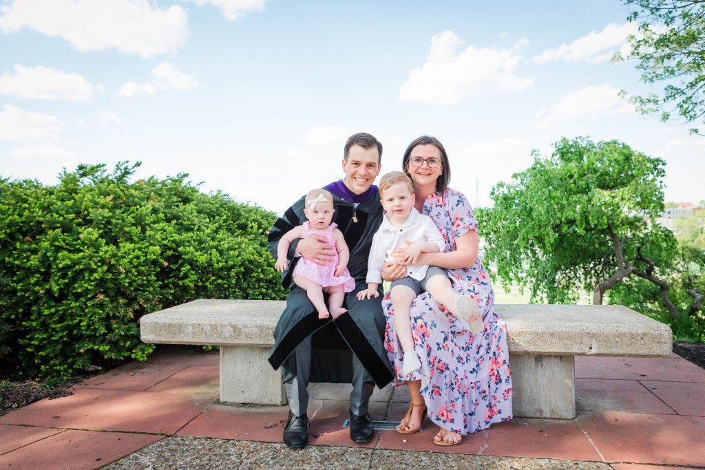 Blake Saffels in graduation regalia with his family